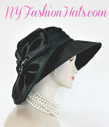 Ladies Black Wide Brim Dressy Satin Polyester Designer Fashion Hat For Special Occasion. This formal satin hat is available in magenta fuchsia hot pink, navy blue, White, black, chocolate brown, and purple. This elegant women's hat can be worn with the bow toward the front or toward the back of the head. A perfect hat for a bride, bridesmaid, or mother of the bride or groom. This Couture Satin Designer Hat Is Sold By NY Fashion Hats Millinery, www.nyfashionhats.com