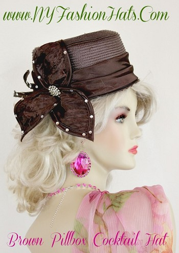 Women's Chocolate Brown Designer Pillbox Cocktail Hat, With A Satin Bow And Feathers.  Beautiful Crystal Rhinestones Are Placed Within The Bow, And Feathers.  This Custom Hat, Is Available In Ivory, Red, Black, Royal Blue, And Chocolate Brown.  We Specialize In Cocktail Hat For Women Pillbox Hats With Veils, Wedding Fascinators, Hats With Feathers, Satin Dress Hats For Women, Hairband Hats, Bridal Headpieces, Hats For Brides, Hair Accessories For Women, Custom Designer Hats, Kentucky Derby Hats, Hats For Horse Races, Hats For Formals, Church Hats, And Special Occasion Hats.  Custom Made And Designed By NY Fashion Hats Custom Millinery Headwear.  http://www.nyfashionhats.com