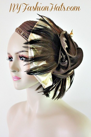 Women's Fashion Designer Haute Couture Brown Satin Ribbon Hat Trimmed With A Large Metallic Gold Lame Fabric Bow, Enhanced With Expensive Brown Feathers. A Beautiful Brown Glass Beaded Metallic Trim Encircles The Crown Of This Custom Made Headpiece. A Brown Satin Bow Is Placed In The Center Of The Brown Feathers. A Lovely Hat Pin Is Included To Hold The Hat Onto Your Head. This Formal Gatsby Styled Hat Can Be Worn In Different Positions, Can Also Be Worn As A Pillbox Hat. This ladies hat is appropriate to wear for the Kentucky Derby, Melbourne Cup, Royal Ascot, horse races, Saratoga racing, Church, formals, weddings, and special occasion. This lovely hat is also suited for mother of the bride or a bride. This Special Occasion Hat Is Custom Made And Designed By NY Fashion Hats Millinery, www.nyfashionhats.com