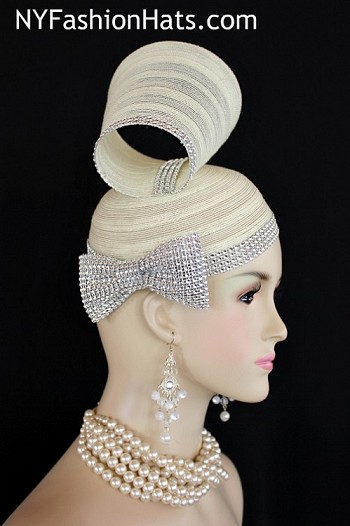 Women's Designer Ivory Formal Special Occasion Wedding Shaped Pillbox Cocktail Hat Wedding Fascinator Bridal Headpiece. This Fashion Hat Is Available In Ivory, Black, Lavender, Red, Light Pink, Dark Brown, Baby Blue, And Camel Beige. This Couture Church Hat Is Embellished With A Sculptured Shape, Adorned With Acrylic Rhinestones. Acrylic Rhinestones Encircle The Lower Edge Of The Crown Of This Fashion Hat. A Beautiful Rhinestone Bow Is Added For A Classic Timeless Affect. This Formal Art Deco Styled 1920's Style Flapper Hat Wedding Headpiece Can Be Worn In Different Positions.  This ladies bespoke couture formal designer wedding fascinator hat is appropriate to wear for horse races, The Kentucky Derby, The Dubai World Cup, The Royal Ascot, The Melbourne Cup, Belmont Stakes, The Preakness Stakes horse racing, Church, weddings, and special occasion. This lovely Spring and Summer fascinator is also suited for mother of the bride or a bride. This Unique Hat Will Make A Fashion Statement. This Special Occasion Hat Is Custom Made And Designed By NY Fashion Hats Millinery, http://www.nyfashionhats.com