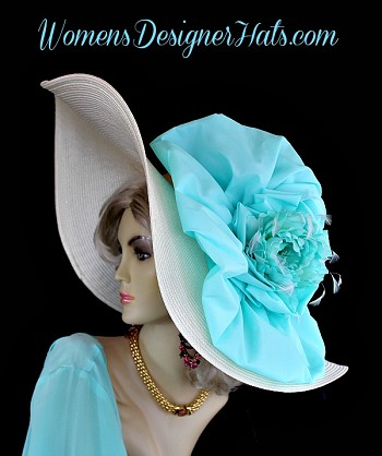 Ivory Wide Brim Haute Couture Designer Kentucky Derby Fashion Hat For Women. This Designer Dress Hat Is Trimmed With A Fabric Aqua Blue Bow, Enhanced With A Custom Dyed Turquoise Blue Silk Millinery Flower. Delicate Ivory Feathers Are Placed Around The Flower For Added Design. This Versatile Hat Can Be Worn In Different Positions. This Feminine Hat Has Such A Romantic Feel. This Exquisite Southern Belle Hat, Is Custom Made And Designed By WomensDesignerHats.com. We Specialize In Formal Hats For Women, Custom Hats For Women, High Fashion Hats, Haute Couture Hats, Wedding Hats, Kentucky Derby Hat, Ladies Dress Hats, Church Hats, And Special Occasion Hats.