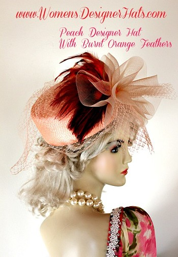 Ladies Peach Cocktail Hat With A Peach Bow, A Veil And Burnt Orange Feathers. This Designer Hat Is Custom Made And Designed By WomensDesignerHats.com