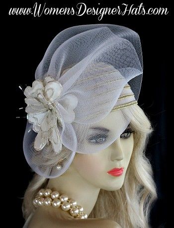 White And Metallic Gold Haute Couture Designer Fashion Bridal Cloche Hat For Women. This Fashion Hat Headpiece Is Trimmed With A Large Sheer White Crin Bow Enhanced With A Custom Made White Satin Beaded Abstract Flower. This Formal Hat Can Be Placed In Any Desired Position On Your Head. This Exquisite Hat, Is Custom Made And Designed By WomensDesignerHats.com. We Specialize In Formal Hats For Women, Custom Hats For Women, Hats For Brides, Bridal Hats, High Fashion Hats, Wedding Hats, Kentucky Derby Hat, Ladies Dress Hats, Church Hats, And Special Occasion Hats.