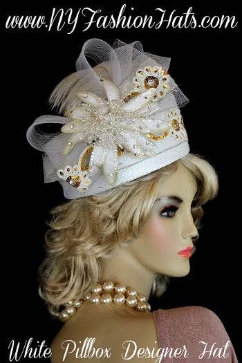 Ladies Women's White Flat Top Pillbox Designer Hat, With A White Netting Bow, Accented With Metallic Gold And White Floral Sequin Trim.  A Large White Fabric Flower, With Bursting White Pearls, White Sequin, And Rhinestones, Gives This Fashion Hat Such Style.  The Same Beautiful Gold And White Sequin Trim Wraps Around The Crown Of This Dress Hat.  A White Ostrich Feather Is Placed Over The Crown.  We Specialize In Cocktail Hats For Women, Pillbox Hats With Veils, Wedding Fascinators, Hats With Feathers, Satin Dress Hats For Women, Hairband Hats, Bridal Headpieces, Hats For Brides, Hair Accessories For Women, Custom Designer Hats, Kentucky Derby Hats, Hats For Horse Races, Hats For Formals, Church Hats, And Special Occasion Hats.  Custom Made And Designed By NY Fashion Hats Custom Millinery Headwear.  http://www.nyfashionhats.com